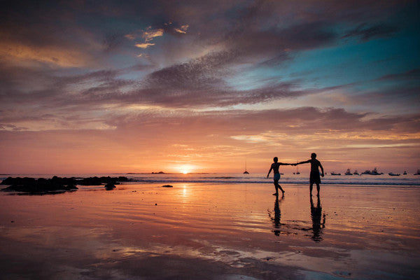 Couple walking on the beach during sunset in Tamarindo, Costa Rica.  Photographed by Kristen M. Brown, Samba to the Sea at The Sunset Shop.