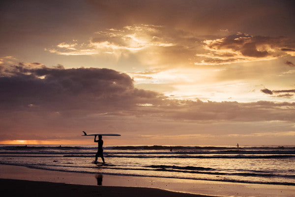Surfer walking on the beach during sunset in Playa Tamarindo, Costa Rica. Photographed by Kristen M. Brown, Samba to the Sea at The Sunset Shop.