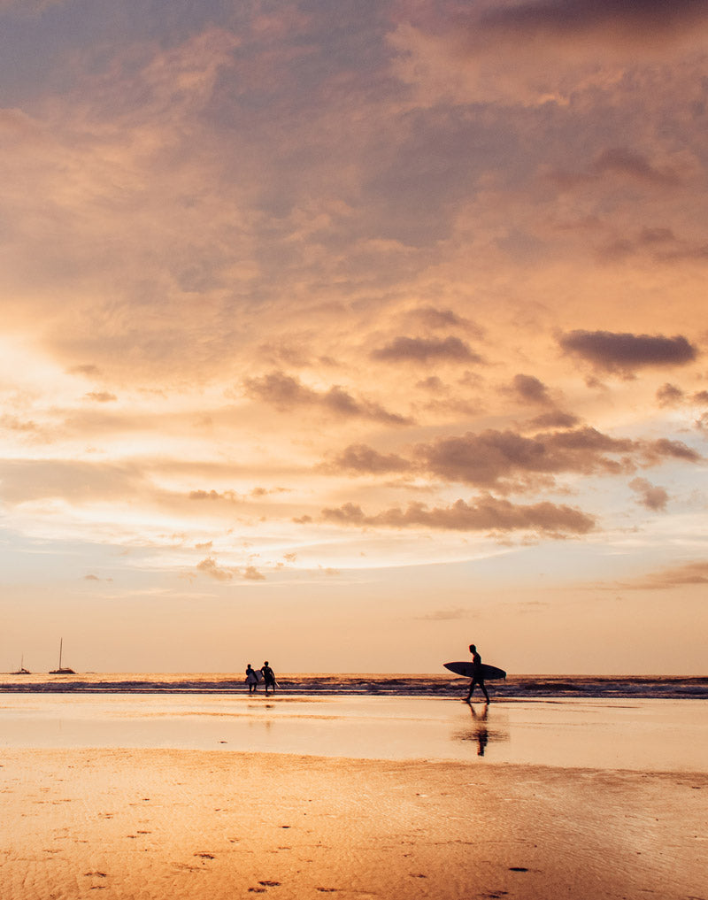 Surfers at sunset in Tamarindo Costa Rica. Photographed by Kristen M. Brown, Samba to the Sea for The Sunset Shop.