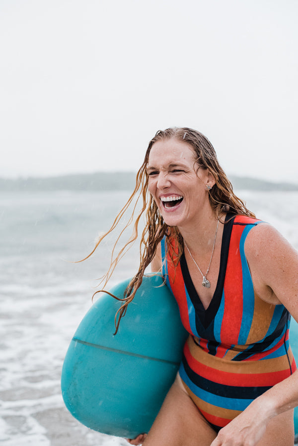 Portrait of Kristen M. Brown of Samba to the Sea holding her surfboard in the rain in Tamarindo Costa Rica.