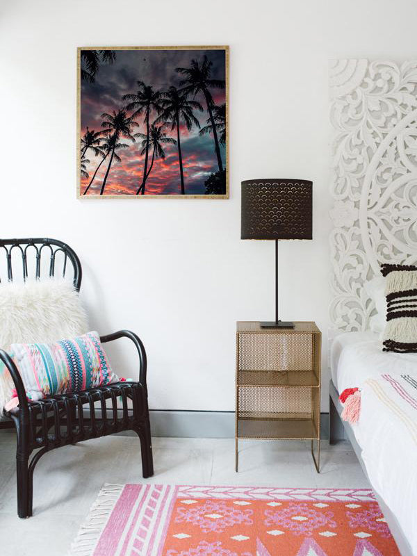 Boho chic bedroom with framed sunset beach print. Palm tree sunset sky in Costa Rica. Black rattan chair, Urban Outfitters rug, Target home decor, . Photographed by Samba to the Sea for The Sunset Shop.