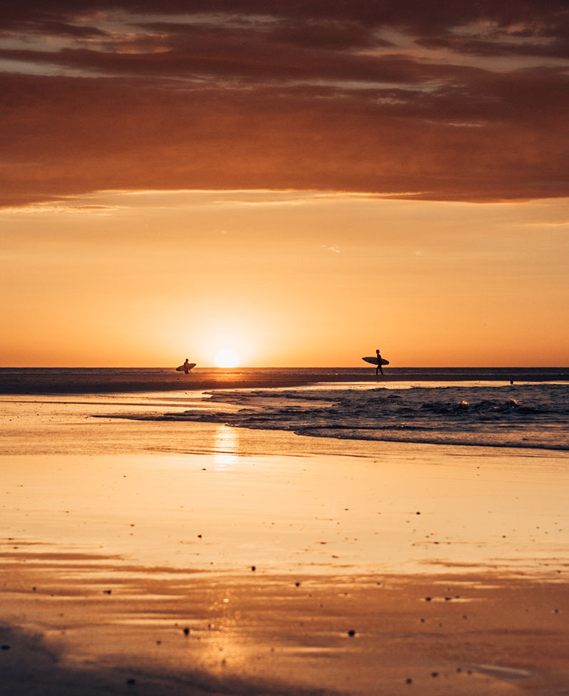 Surfers walking on the beach during sunset in Tamarindo Costa Rica. Surfer art pictures photographed by Kristen M. Brown, Samba to the Sea for The Sunset Shop.