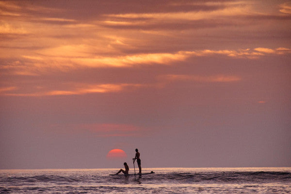SUP paddling during sunset in Tamarindo, Costa Rica. Photographed by Kristen M. Brown, Samba to the Sea at The Sunset Shop.