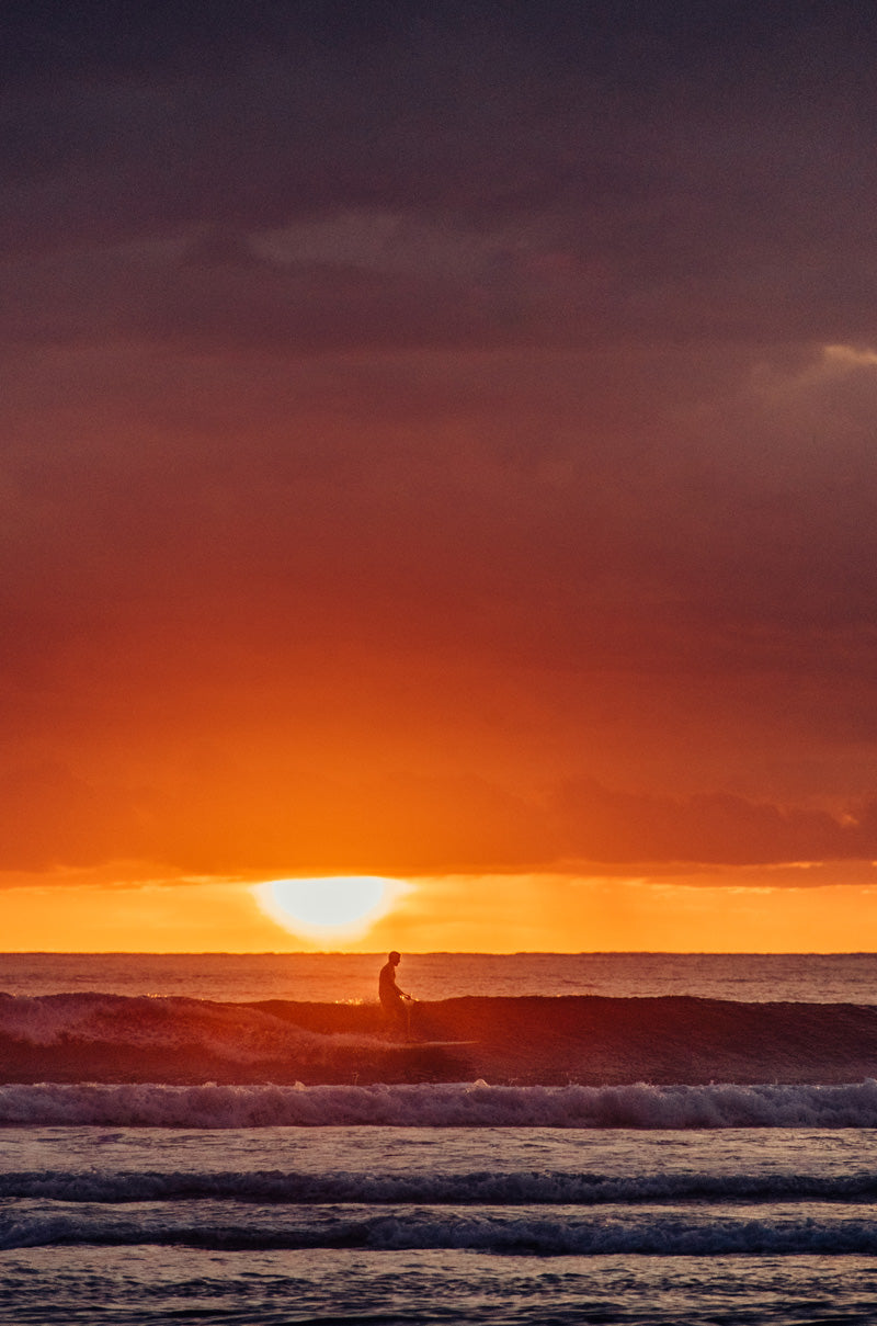Surfer riding a wave during sunset in Tamarindo Costa Rica during sunset. Photographed by Kristen M. Brown, Samba to the Sea for The Sunset Shop.