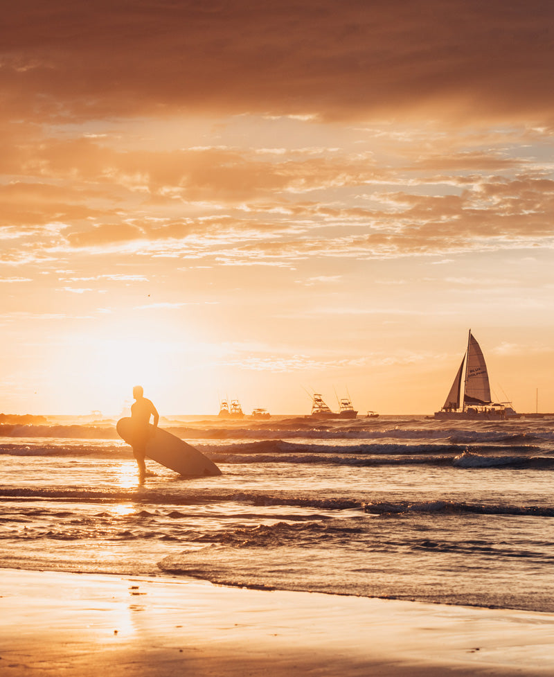 Surfer walking on the beach during sunset in Tamarindo Costa Rica. Photographed by Kristen M. Brown, Samba to the Sea for The Sunset Shop.