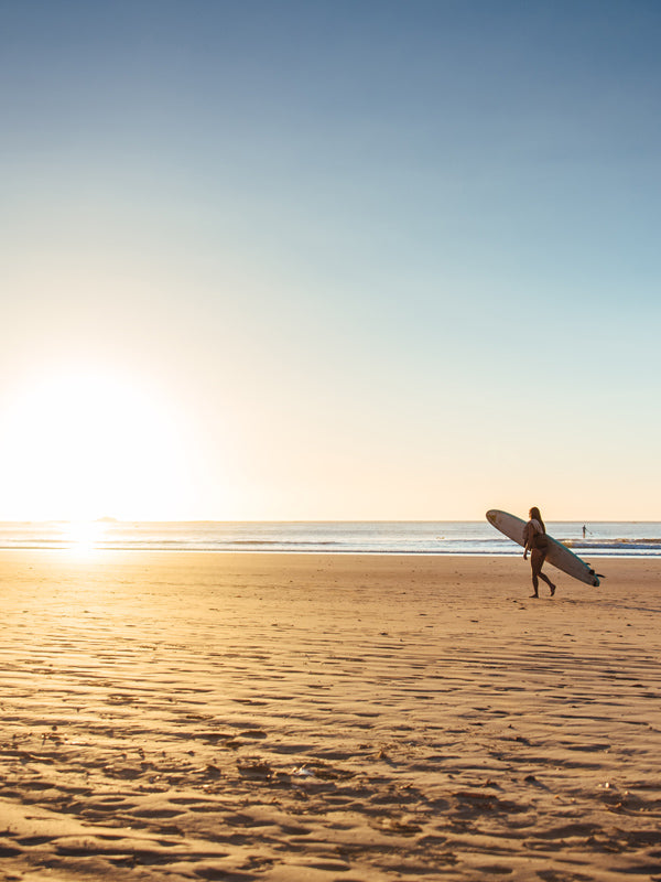Surfer walking on the beach during sunset in Tamarindo Costa Rica. Sunset art pictures photographed by Kristen M. Brown, Samba to the Sea for The Sunset Shop.