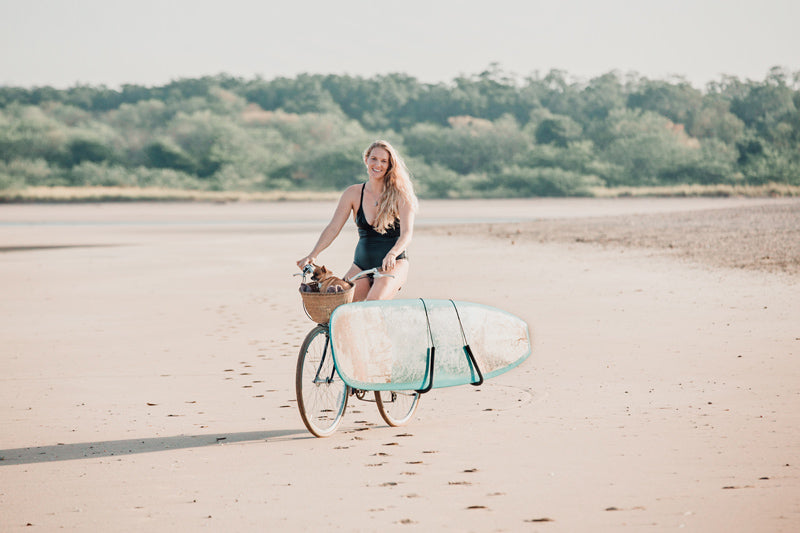 Female surfer on the beach in Tamarindo Costa Rica. MI OLA bikini, Schwinn bike, Chihuahua in a Nantucket bike basket, surfboard rack on bike, Ricky Carroll surfboard Super Con Ugly. Kristen M. Brown for Samba to the Sea.
