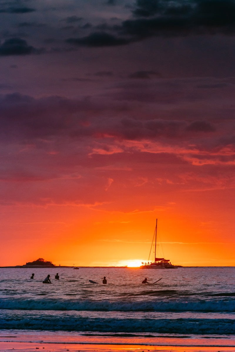 Surfers during sunset in Tamarindo Costa Rica. Photographed by Kristen M. Brown, Samba to the Sea for The Sunset Shop.