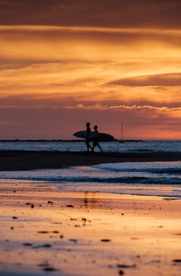 Surfers walking on the beach during a golden sunset in Playa Tamarindo, Costa Rica. Photographed by Kristen M. Brown, Samba to the Sea.