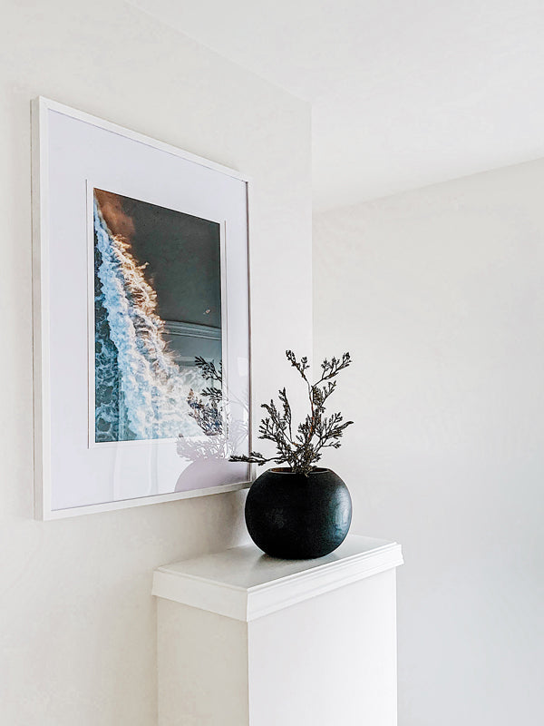 "Framed aerial surfer print ""The Rush"" from The Sunset Shop by Ash Interiors. Aerial surfer print by Samba to the Sea at The Sunset Shop. Image is an aerial photo of surfer paddling out to surf in Tamarindo, Costa Rica during golden hour."