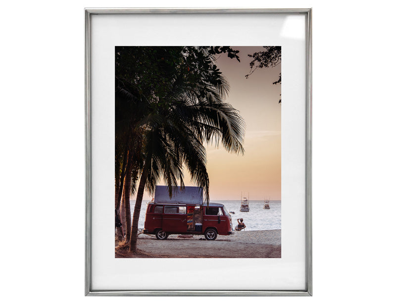 VW bus parked under a palm tree at the beach during sunset in Costa Rica. The Sunset Shop by Samba to the Sea.