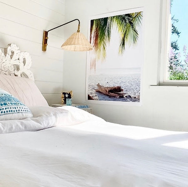 "White coastal bedroom with tropical palm tree photo print. Surf shack and beach bungalow vibes. ""Via Paradise"" beach print by Kristen M. Brown of Samba to the Sea for The Sunset Shop."