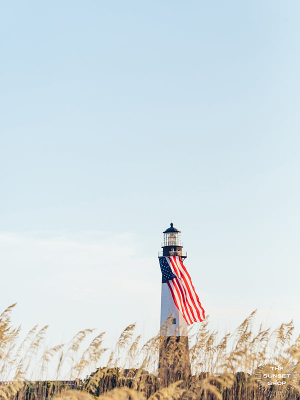 "There she was, dancing in the sea breeze with the sea grass and shimmering in the late afternoon sun! Majestic American flag hanging from the Tybee Island Lighthouse in Tybee Island, GA. ""American Beauty"" photographed by Kristen M. Brown, Samba to the Sea for The Sunset Shop."