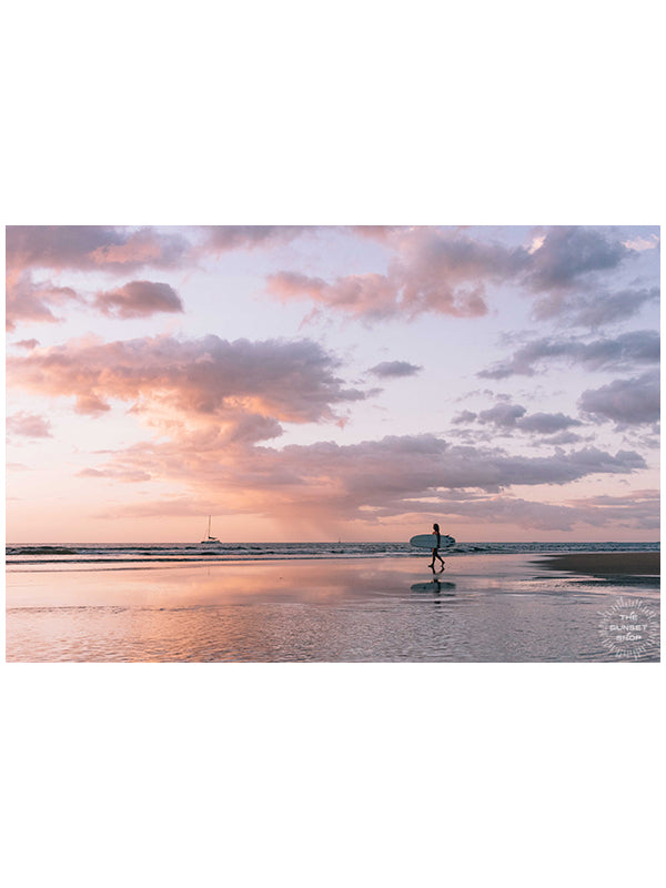 Angel del Mar - Sea Angel sunset surfer girl print by Samba to the Sea at The Sunset Shop. Photo of a female surfer walking on the beach during a pastel pink sunset in Tamarindo, Costa Rica.