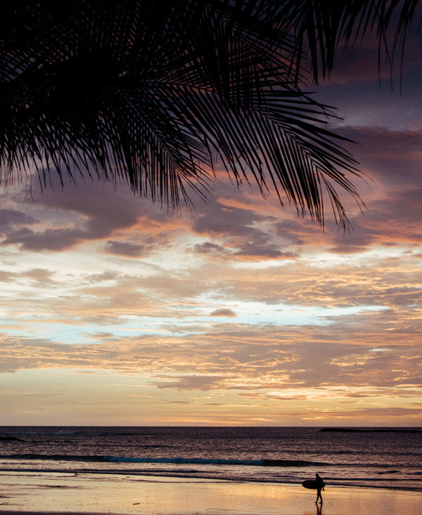 Barefoot Adventures sunset print by Samba to the Sea at The Sunset Shop. Image of a surfer walking on the beach during a stunning sunset in Tamarindo, Costa Rica.