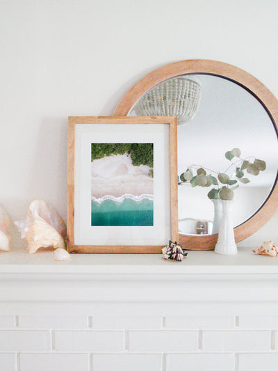 Aerial image of white sand beach and turquoise water of the beach at Playa Conchal, Costa Rica. Aerial beach print by Samba to the Sea at The Sunset Shop. Coastal living framed aerial beach print shelfie on white fireplace mantle.