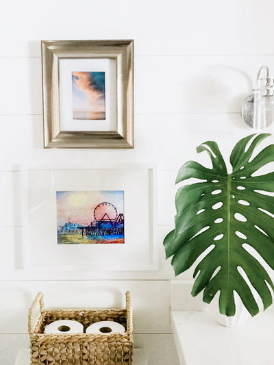 Beautiful shiplap white coastal bathroom with a breathtaking sunset print by Samba to the Sea and watercolor painting.