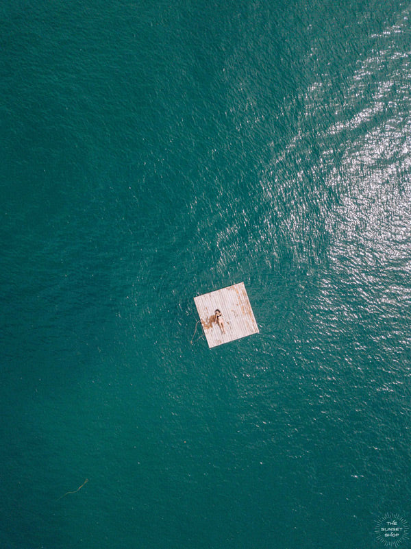 Woman laying on raft in the turquoise ocean Las Catalinas, Costa Rica. Photographed by Samba to the Sea for The Sunset Shop.