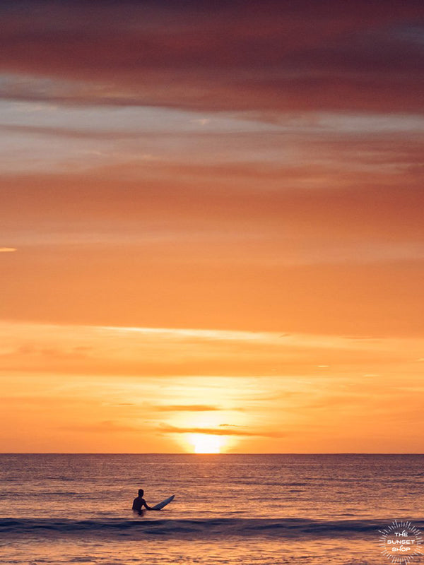 Surfer watching a golden orange sunset in the ocean in Tamarindo Costa Rica. Photographed by Kristen M. Brown, Samba to the Sea.