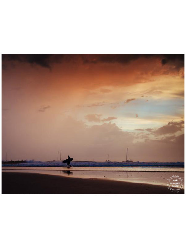 Dance to the Song of the Sea print featured on Apartment Therapy by Samba to the Sea at The Sunset Shop. Photo of a surfer walking on the beach during a pink sunset in Tamarindo, Costa Rica.