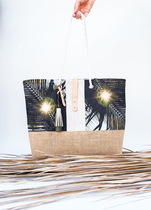 """Dreaming Under A Palm Tree"" beach bag is the perfect bag to help you bring a piece of your tropical happy place with you, no matter where you may live. Palm tree print beach bag with leather tassels and cotton sailor rope. Chapman at Sea x Samba to the Sea collaboration."