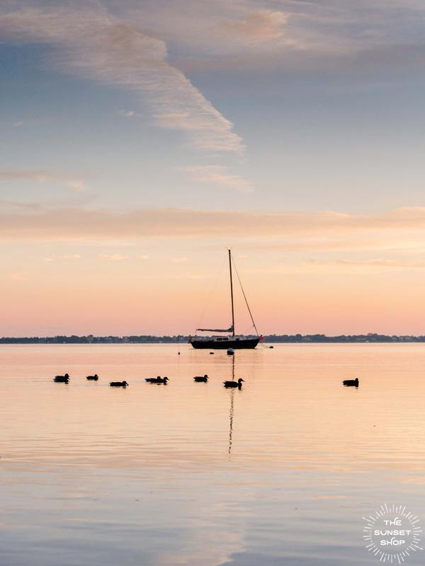 Take a deep breath and welcome a beautiful new day with a serene sunrise sky over the bay. Sunrise image of ducks swimming past a sailboat in the bay in Huntington, NY. Photographed by Kristen M. Brown, Samba to the Sea.
