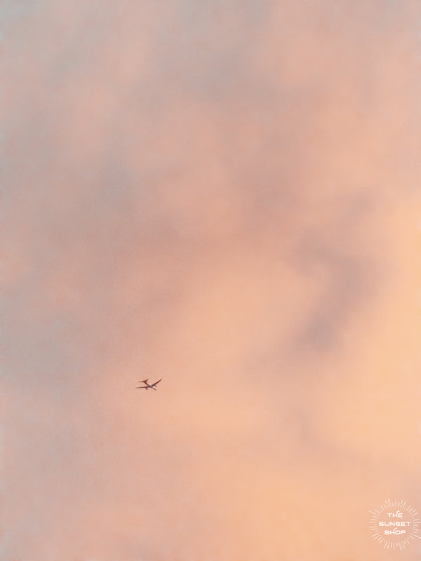 Airplane flying in a sunset sky in Miami, Florida. Photographed by Kristen M. Brown of Samba to the Sea, The Sunset Shop.