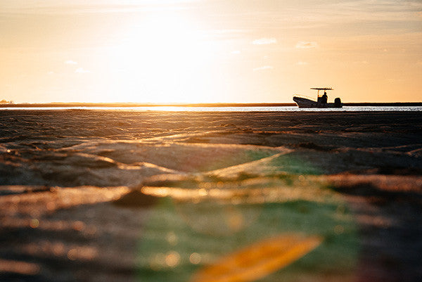 Golden Season print by Samba to the Sea at The Sunset Shop. Image of a Panga boat and low tide golden sand during sunset in Tamarindo, Costa Rica.