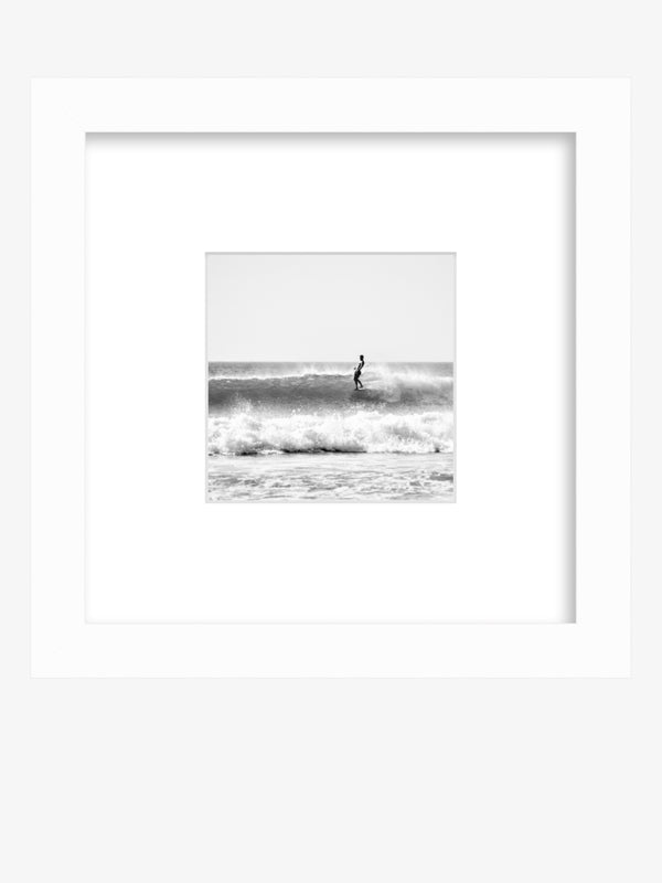 Black and white surfer framed shelfie print. Wingnut from Endless Summer hanging five surfing in Tamarindo Costa Rica.Wingnut from Endless Summer hanging five surfing in Tamarindo Costa Rica. Photographed by Kristen M. Brown Samba to the Sea at The Sunset Shop.