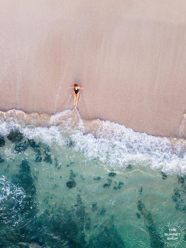 Woman laying on the beach as the waves reach her feet in Costa Rica. Photographed by Samba to the Sea for The Sunset Shop.