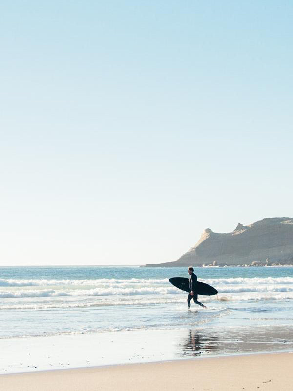 """Surfer walking into the ocean in Cape Kiwanda, Oregon. Photographed by Kristen M. Brown of Samba to the Sea for The Sunset Shop. """"Into the Blue"""" Oregon Coast surfer photo print."""
