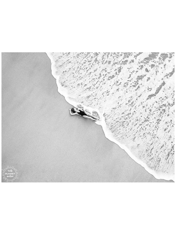 Black and white image of woman laying on the beach as the waves reach her feet in Costa Rica. Photographed by Samba to the Sea for The Sunset Shop.