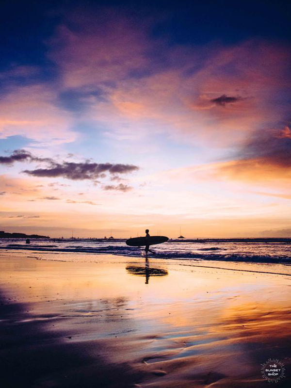 """Live Like a Local"" sunset surfer print by Samba to the Sea at The Sunset Shop. Image of a surfer walking on the beach during a magical sunset in Tamarindo, Costa Rica."