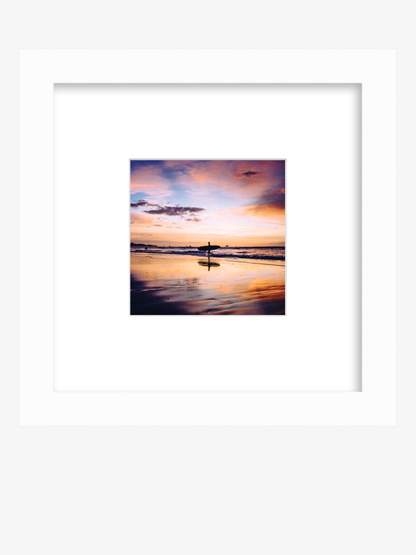 """Live Like a Local"" sunset surfer framed shelfie print by Samba to the Sea at The Sunset Shop. Image of a surfer walking on the beach during a magical sunset in Tamarindo, Costa Rica."