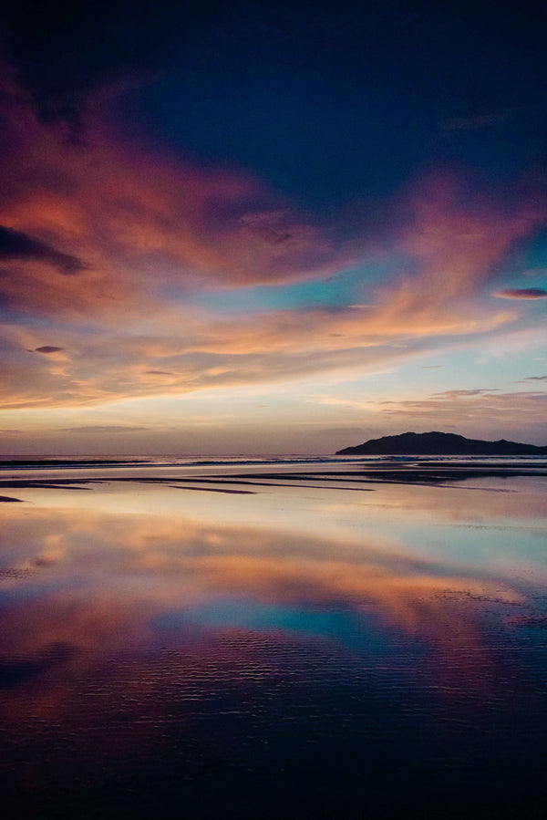 "When the sunset looks like a painting and reflected perfectly like a mirror off the wet sand! Beautiful pink, purple, and turquoise blue sunset sky and reflections off the beach in Tamarindo Costa Rica. ""Paint the Sky"" sunset print by Kristen M. Brown, Samba to the Sea at The Sunset Shop."