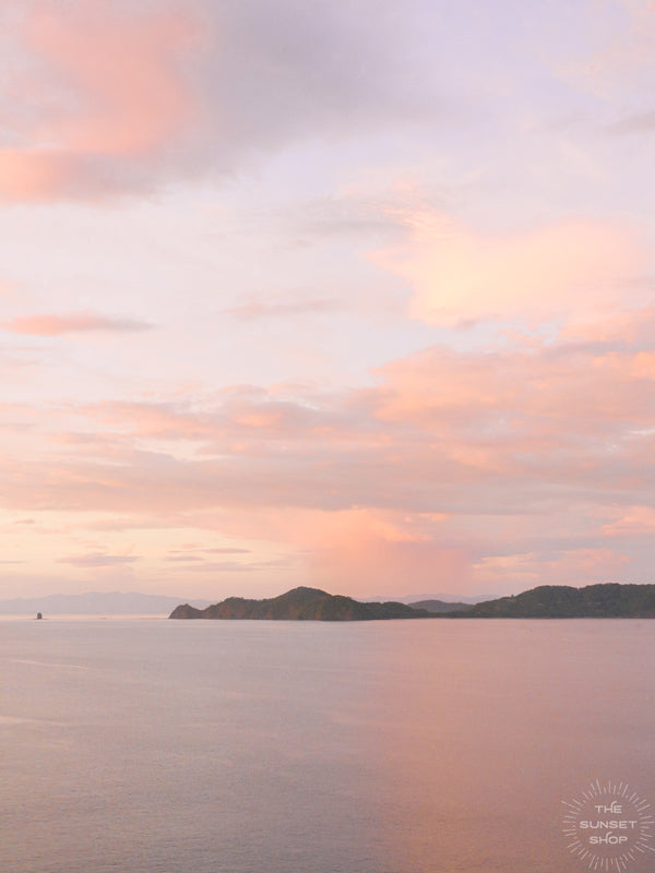 "There is freedom waiting for you, on the breezes of the sky, and you ask, ""What if I fall?"" Oh but my darling, what if you fly? Aerial photo of a pastel sunset casting a pink glow over the ocean in Playa Hermosa Costa Rica."