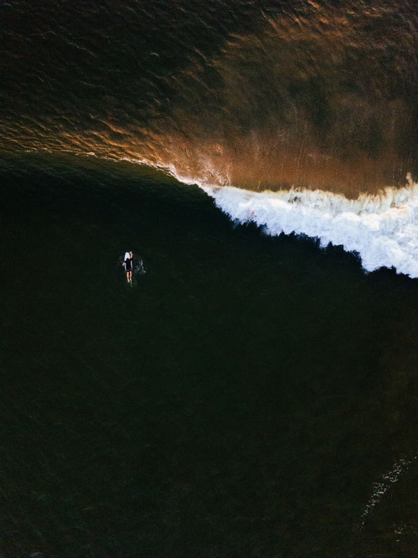 Aerial surfer print by Samba to the Sea at The Sunset Shop. Image is an aerial photo of surfer paddling out to surf in Tamarindo, Costa Rica.
