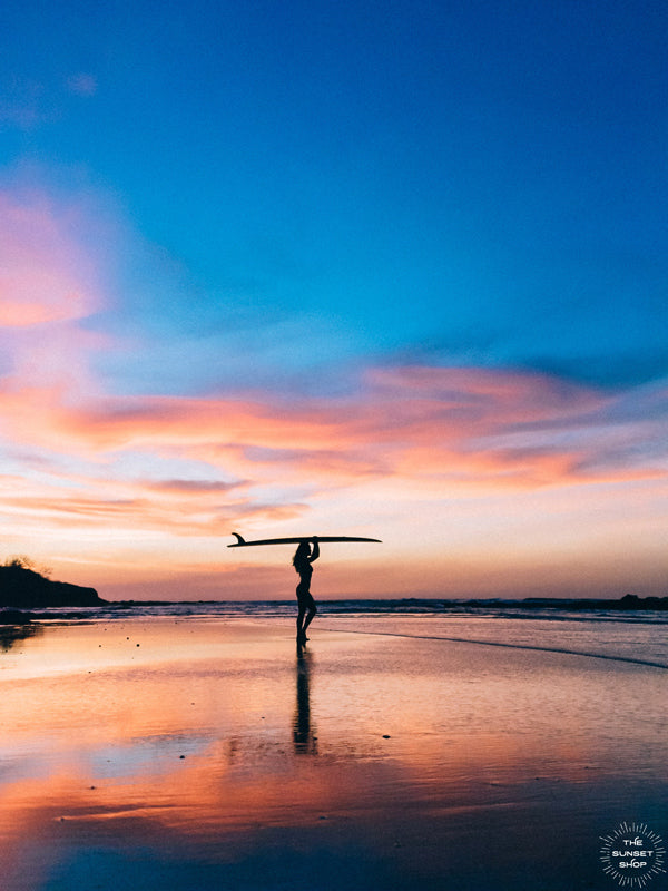 Pura Amor / Pure Love sunset female surfer print by Samba to the Sea at The Sunset Shop. Photo of a female surfer on the beach during a breathtaking sunset in Tamarindo, Costa Rica.