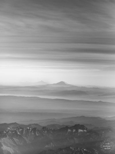 Black and white aerial image of late afternoon sun rays over Mt Rainier in Washington. What a glorious farewell the late afternoon sun gives the mountains. Magical late afternoon sun rays falling over Mt Rainier and the Cascade mountain range in Washington.