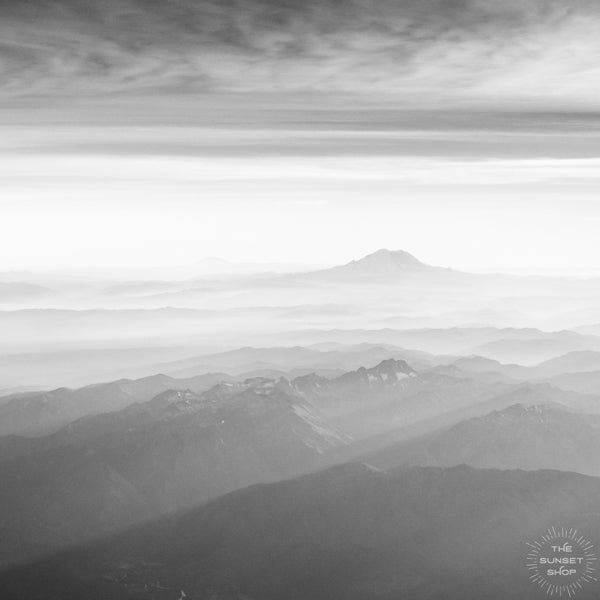 Black and white aerial framed shelfie print image of late afternoon sun rays over Mt Rainier in Washington. What a glorious farewell the late afternoon sun gives the mountains. Magical late afternoon sun rays falling over Mt Rainier and the Cascade range in Washington.