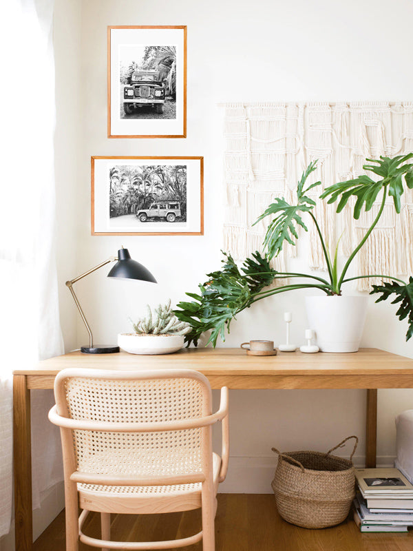Black and white Land Rover photo prints hanging in a boho work from home desk area with hanging macrame, philodendron plant, mini cactus, cane desk chair, and belly basket. Land Rover prints available at The Sunset Shop by Samba to the Sea.