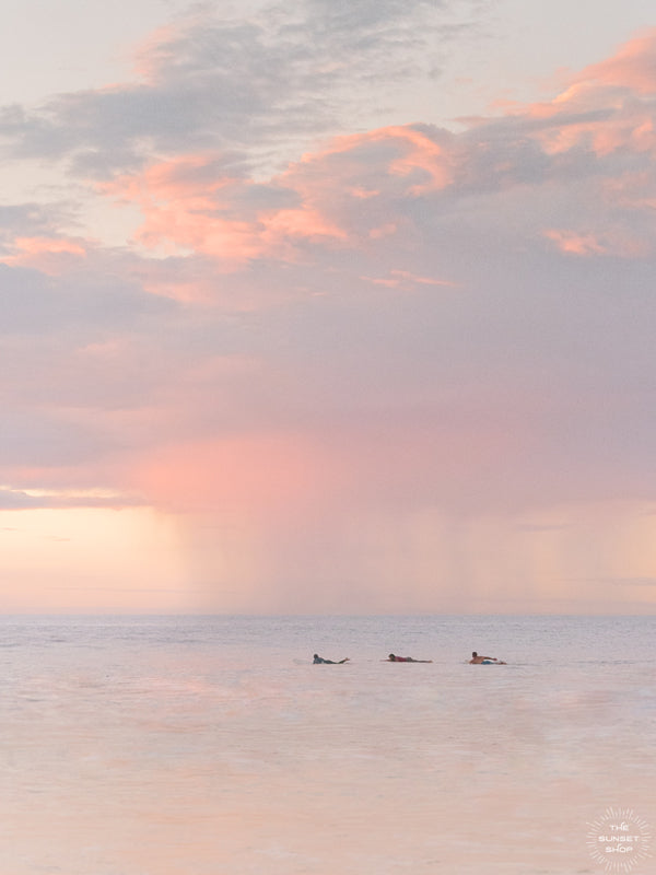 "Surfers paddling in the ocean during a pastel pink rain squall at sunset in Costa Rica. What a surfer's dreams are made of - - beautiful sunset surf sessions. Have a piece of sunset surfer magic in your very own home with ""Saltwater Paradise"" sunset surfer wall art photographed by Kristen M. Brown of Samba to the Sea for The Sunset Shop."