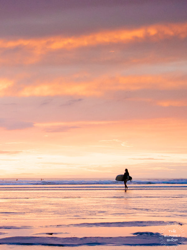 She's Magic sunset surfer print by Samba to the Sea at The Sunset Shop. Photo of a female surfer walking on the beach during a pastel pink sunset in Tamarindo, Costa Rica.
