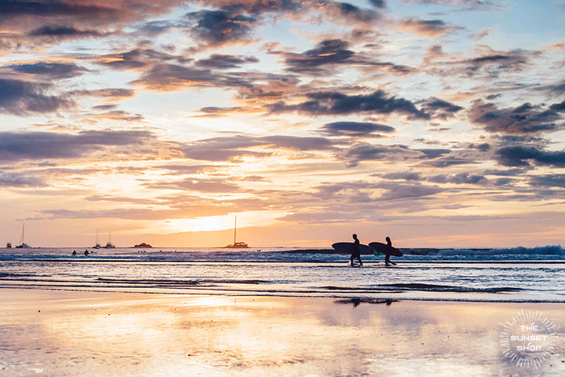 "All you need is love, surf, and sunsets. Welcome back to that magical sunset surf date at the beach in Costa Rica. Surfer couple walking on the beach in Tamarindo Costa Rica. ""Sunset Surf Date"" sunset wall art by Samba to the Sea."