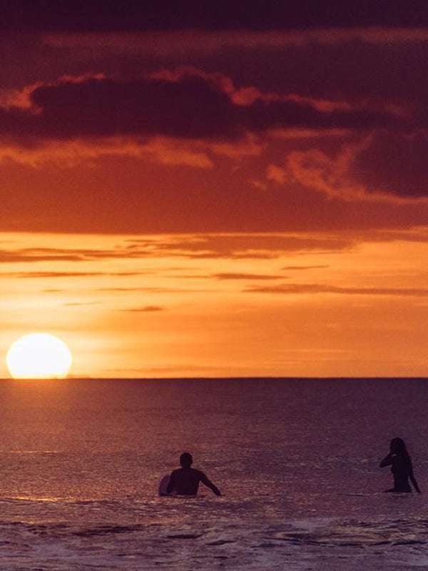 Surf Amor. Surfer couple watching sunset on their surfboards in Tamarindo Costa Rica. Photographed by Kristen M. Brown, Samba to the Sea for The Sunset Shop.