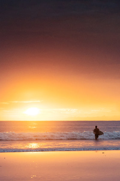 Surfer walking into the ocean with his surfboard during a golden sunset in Tamarindo, Costa Rica. Surfer Glow print by Samba to the Sea at The Sunset Shop.