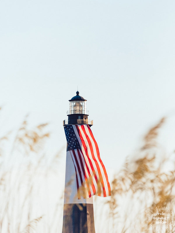 "There she was, dancing in the sea breeze with the sea grass and shimmering in the late afternoon sun! Majestic American flag hanging from the Tybee Island Lighthouse in Tybee Island, GA. ""Sweet Liberty"" photographed by Kristen M. Brown, Samba to the Sea for The Sunset Shop."