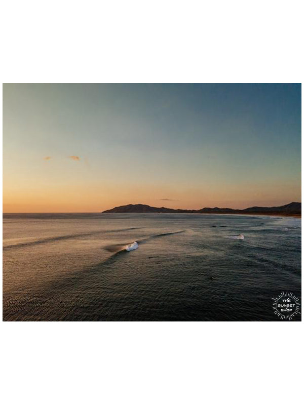 Aerial wave print by Samba to the Sea at The Sunset Shop. Image is an aerial photo of a wave breaking in Tamarindo, Costa Rica.