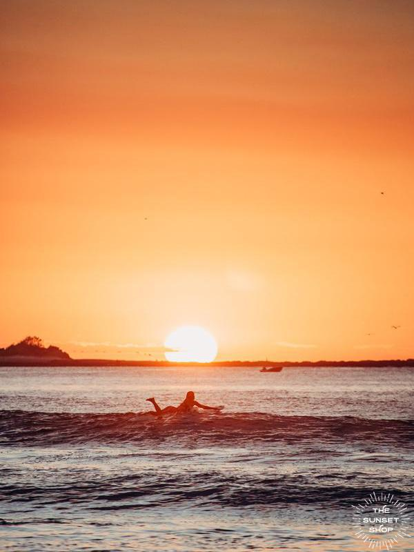 Female surfer paddling out during sunset in Tamarindo, Costa Rica. Photographed by Kristen M. Brown of Samba to the Sea for The Sunset Shop.