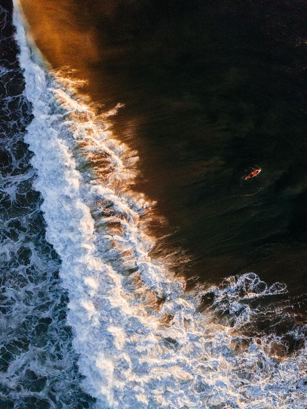 Aerial surfer print by Samba to the Sea at The Sunset Shop. Image is an aerial photo of surfer paddling out to surf in Tamarindo, Costa Rica during golden hour.